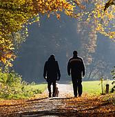 2 people walking dog in park