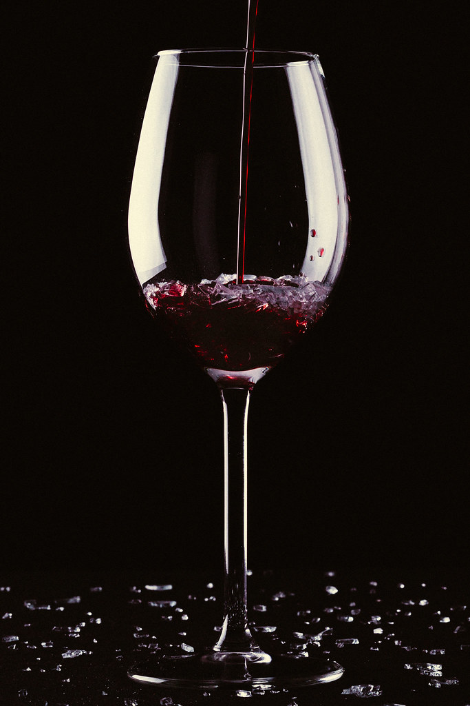 A long Stemmed Glass with Red Wine being poured into the Glass.