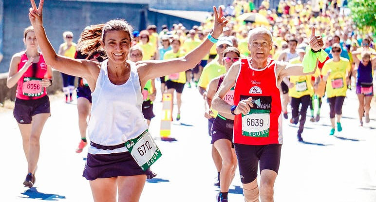 Lady and Man smiling and waving to crowd whilst running in a Race.