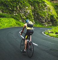 Man Cycling on Downhill Road through Luss gren Mountains.