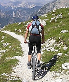Man on Bike on a Track in the Mountains