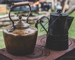 2 Old Kettles sitting on top of a Outdoor wood burning stove
