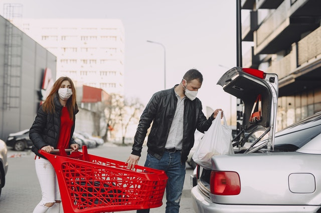 Couple Taking Shopping in Trolley to Car in the Car Park.