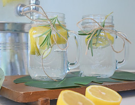 2Glass Jars Full of Water with Lemons and Mint added for flavor
