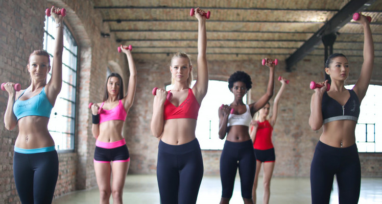 Group of ladies lifting Dumbbells in Gym.